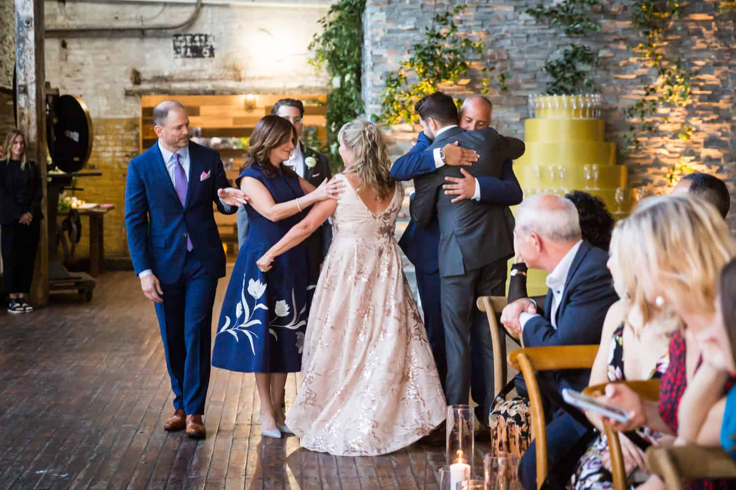 Greenpoint Loft wedding photos of two grooms and respective parents hugging each other in aisle