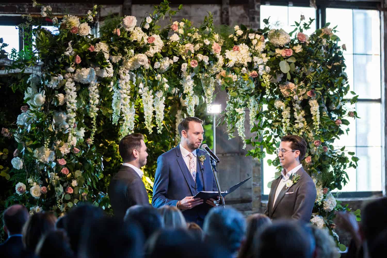 Greenpoint Loft wedding photos of gay wedding ceremony under floral altarpiece