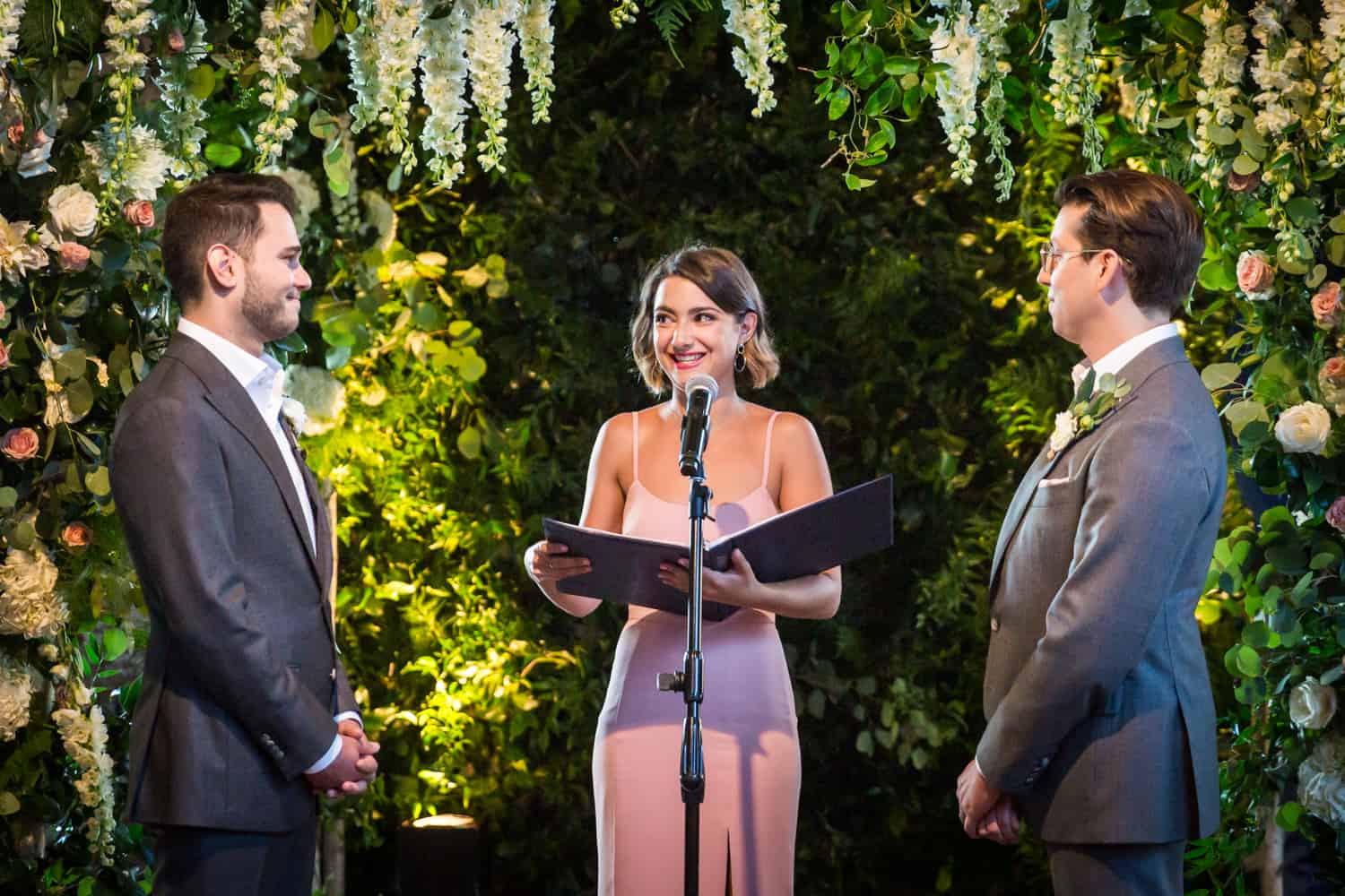 Greenpoint Loft wedding photos of woman speaking between two grooms during ceremony