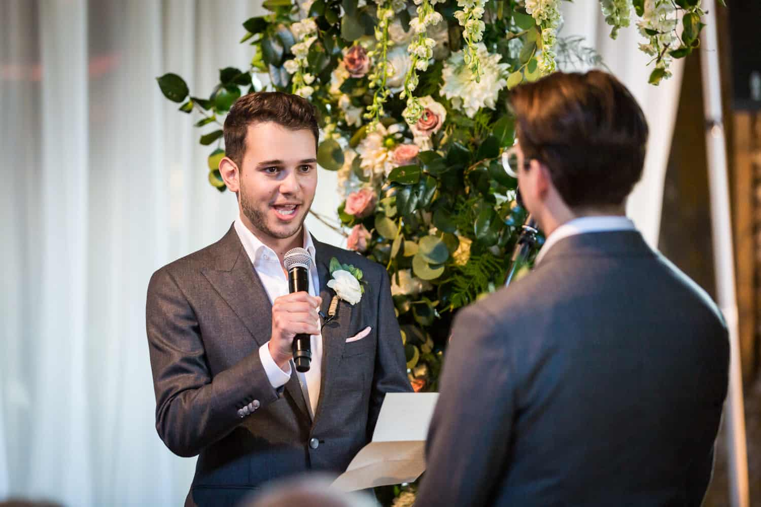 Greenpoint Loft wedding photos of groom saying vows into microphone during ceremony