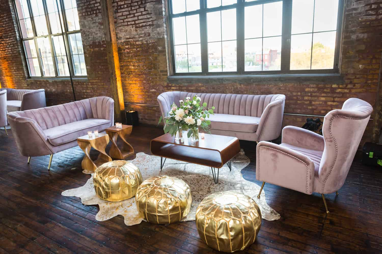Pink velvet couches and gold poofs with coffee table at Greenpoint Loft wedding reception