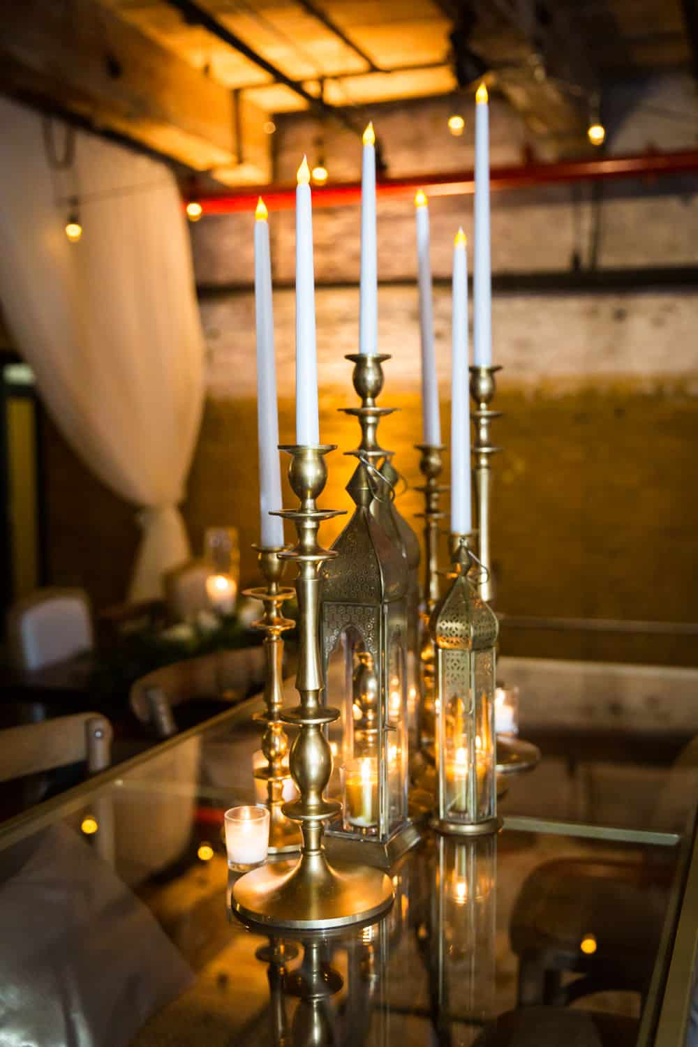 Table with gold candelabras and white tapered candles