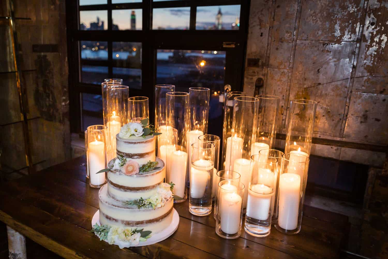 Wedding cake and rows of candles on table with view of NYC skyline through window