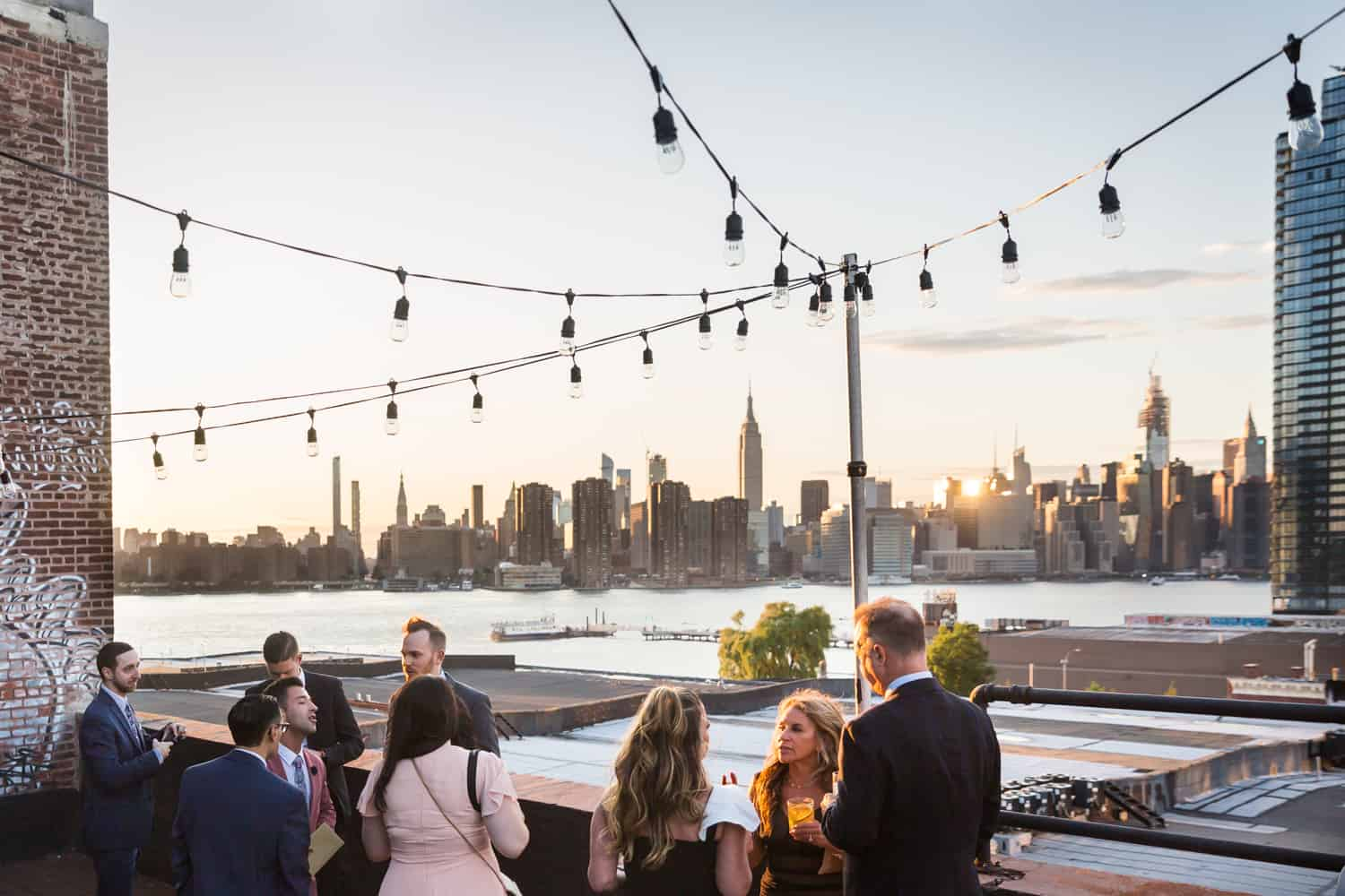 Greenpoint Loft wedding photos of guests enjoying cocktail hour on roof at sunset