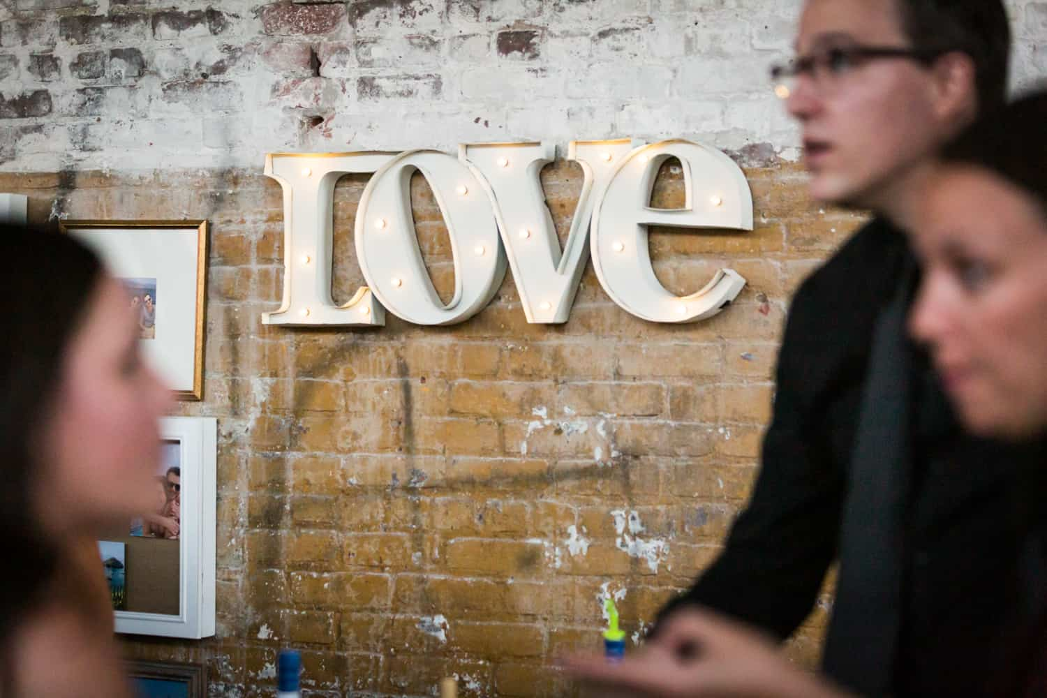 'Love' sign on brick wall with lights
