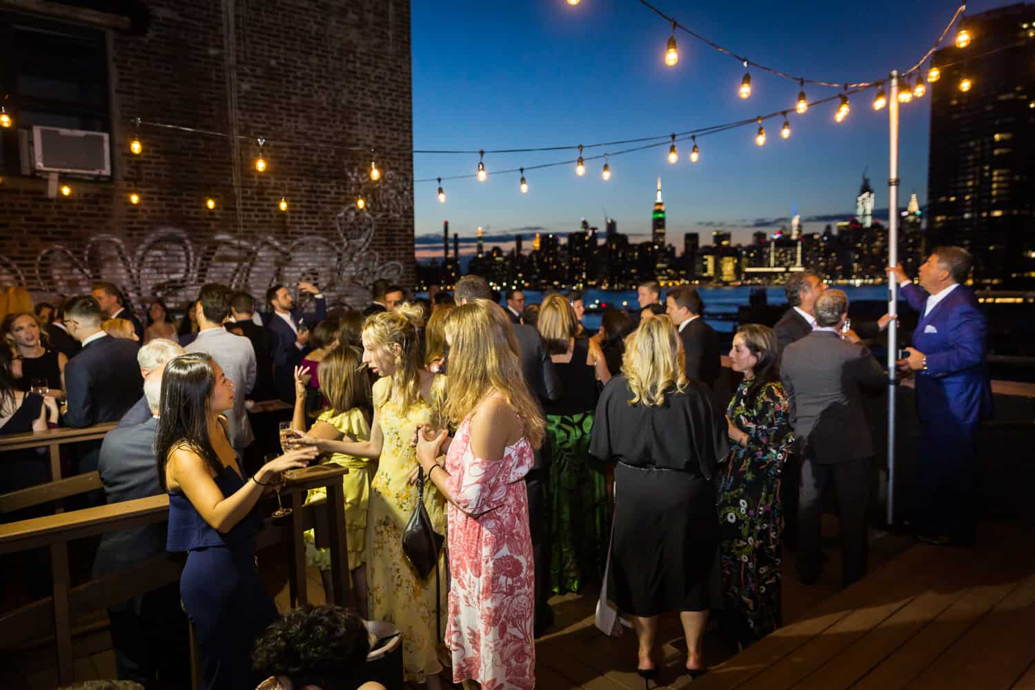 Greenpoint Loft wedding photos of guests enjoying cocktail hour on the roof at night
