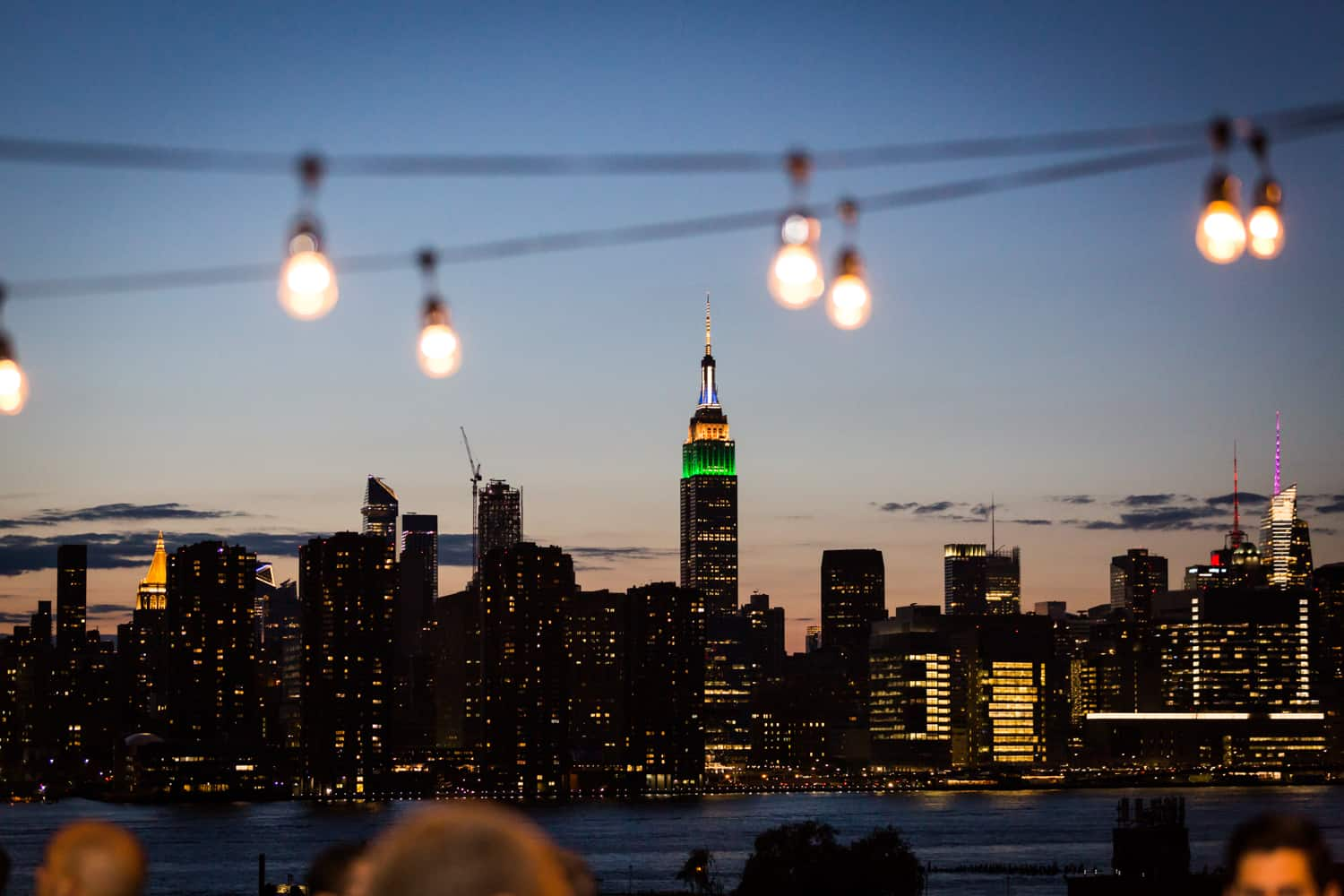 Rooftop view of Empire State Building with strings of lights at dusk