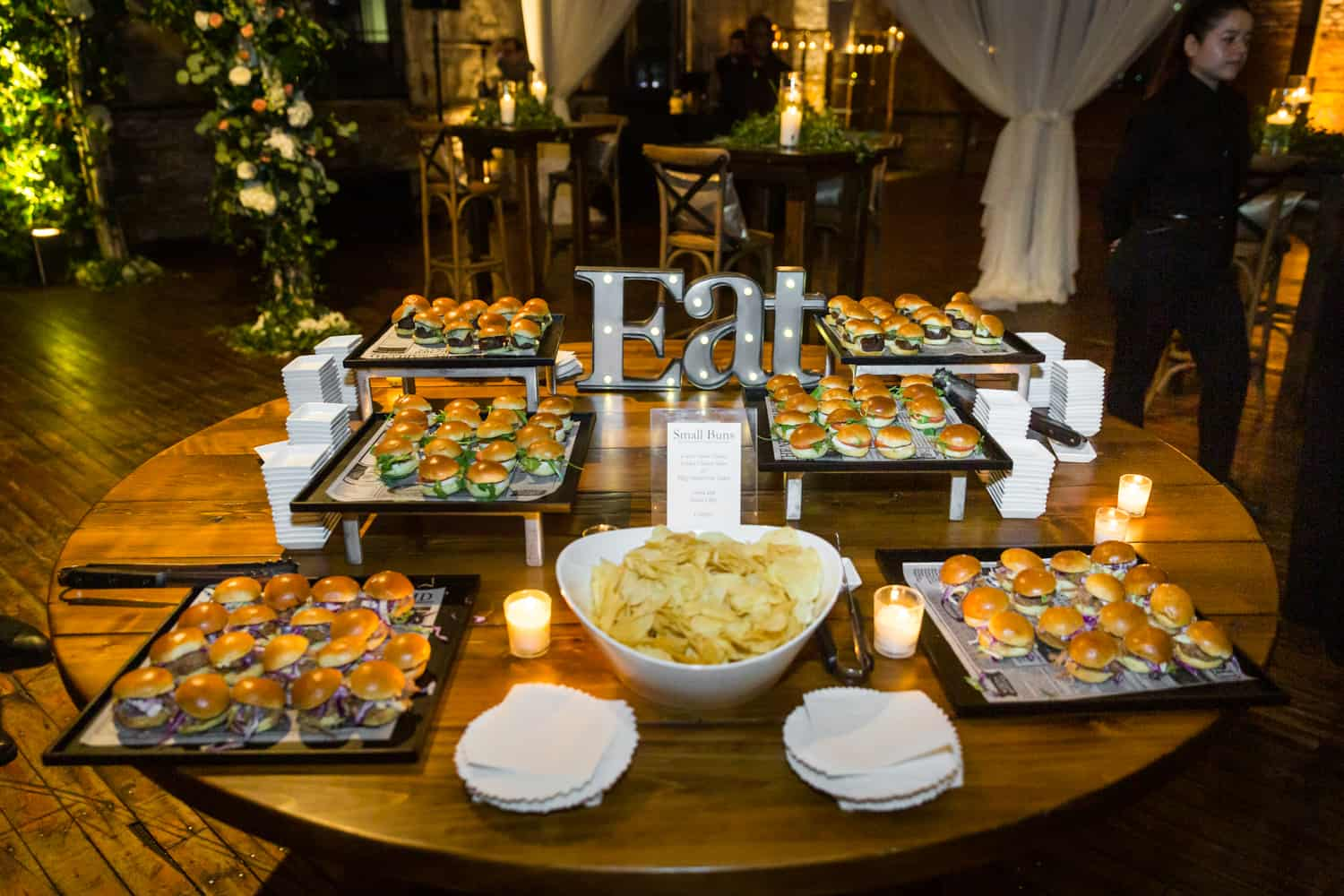 Table filled with plates of mini burgers and 'Eat' sign