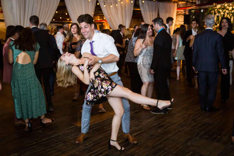Greenpoint Loft wedding photos of man dipping woman on dance floor