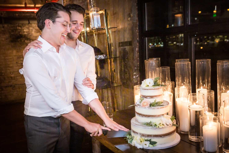 Greenpoint Loft wedding photos of two grooms cutting wedding cake