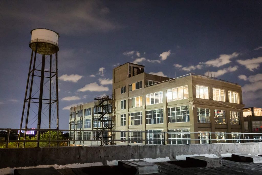 View of Greenpoint, Brooklyn factory building and water tower at night