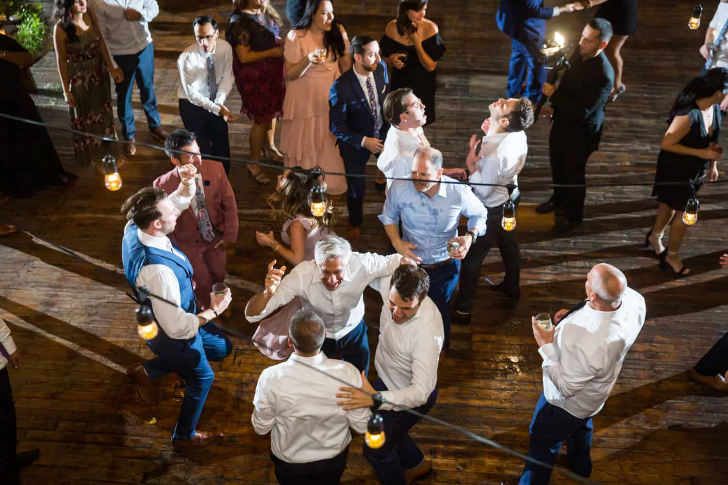 View from mezzanine of guests dancing during gay wedding reception
