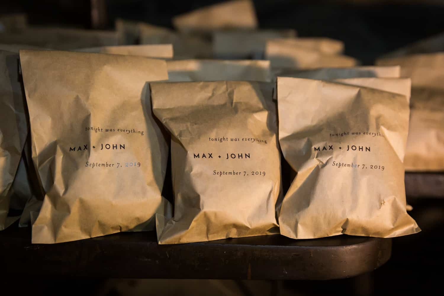 Guest favor brown paper bags with names of grooms on front