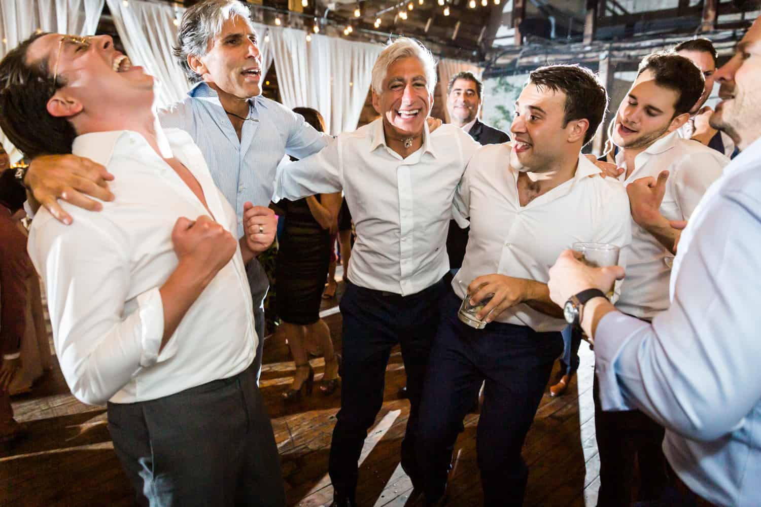 Group of male guests dancing with two grooms at Greenpoint Loft wedding