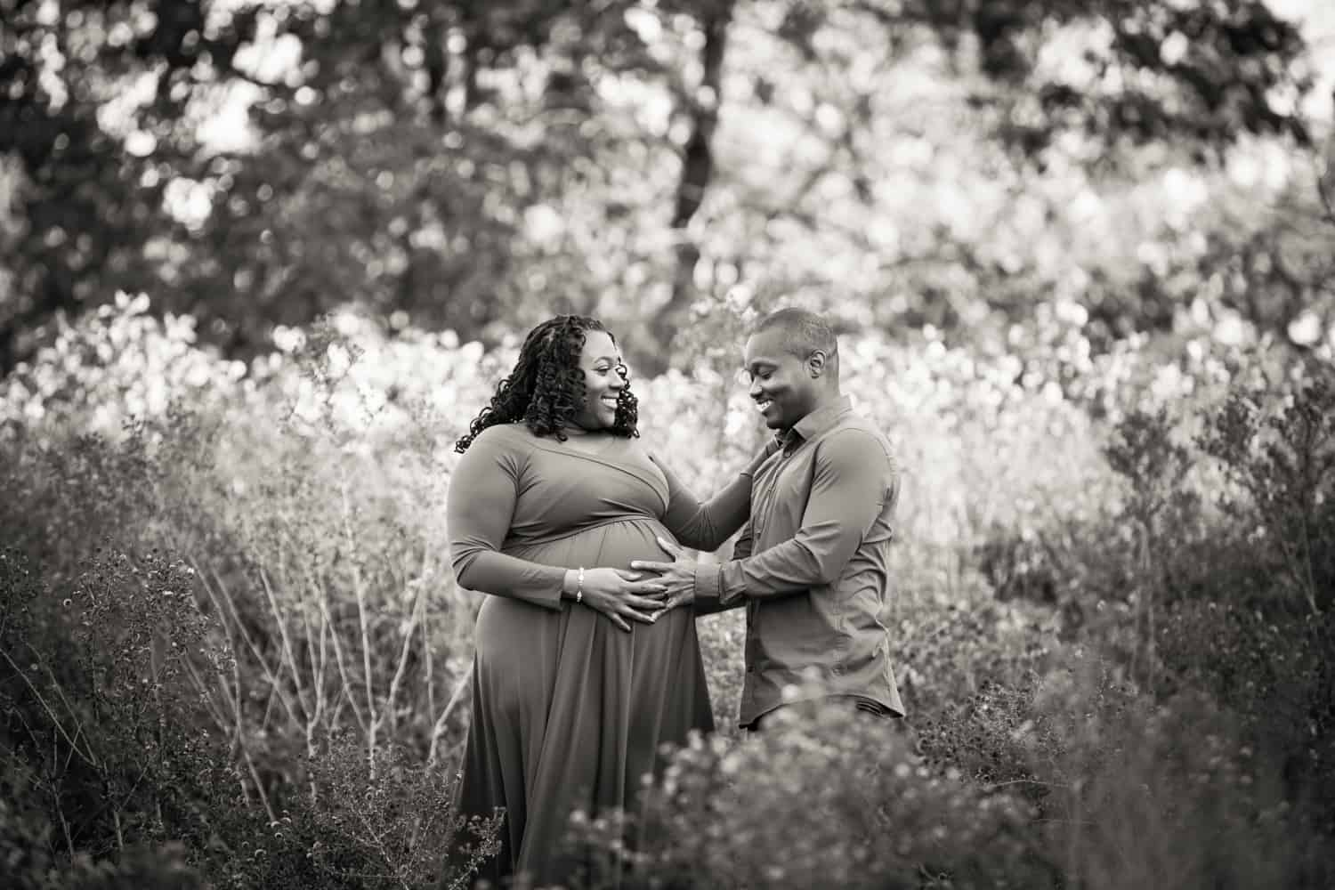 Black and white photo of African American couple during maternity photo shoot in Forest Park