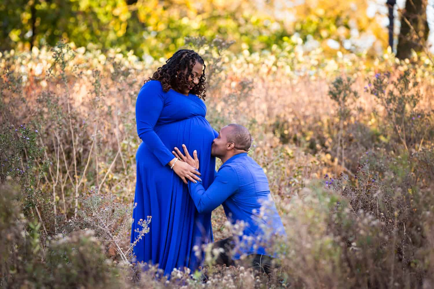 Man kissing wife's pregnant stomach in Forest Park during maternity photo shoot