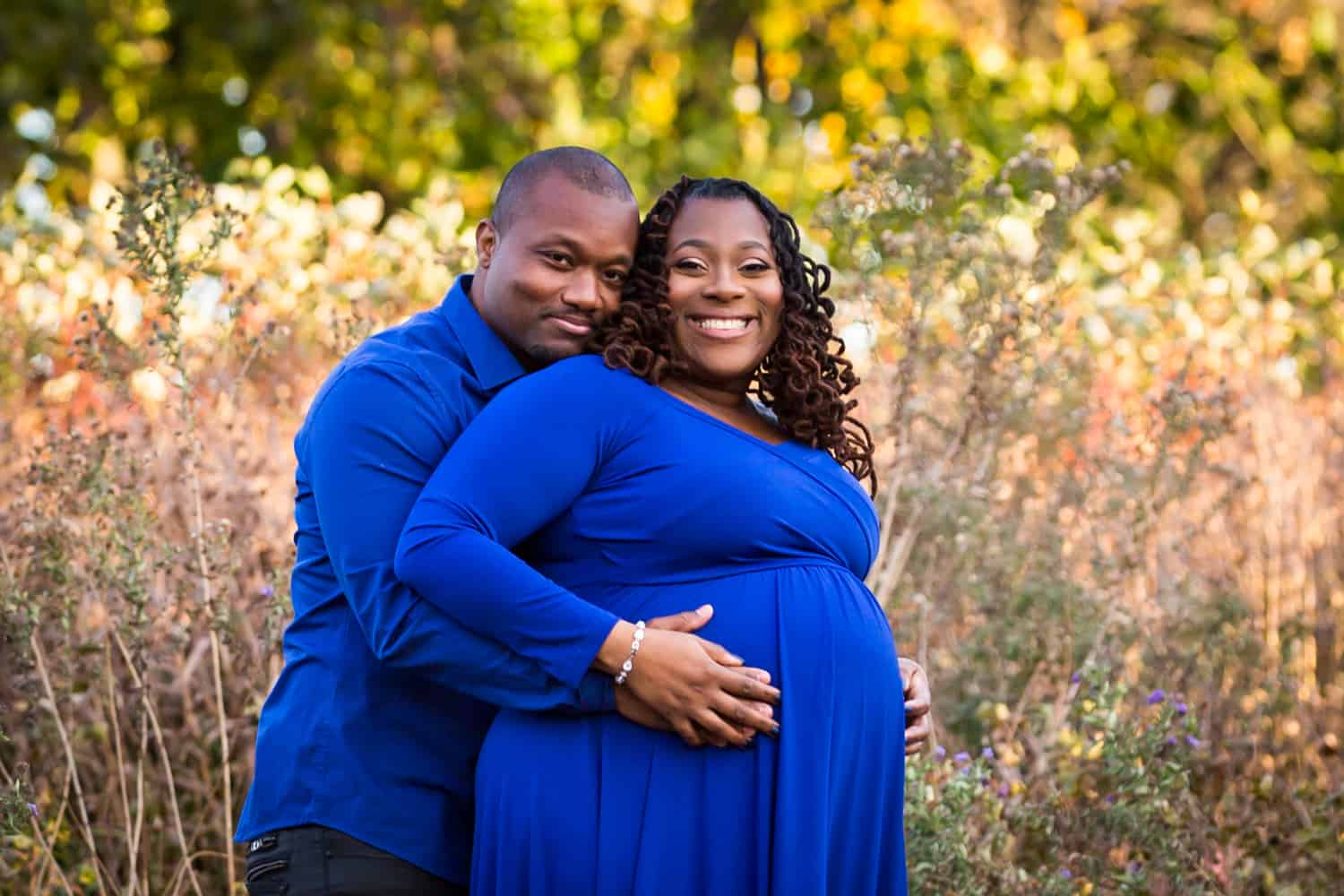 African American couple hugging in Forest Park for an article on maternity photo shoot ideas