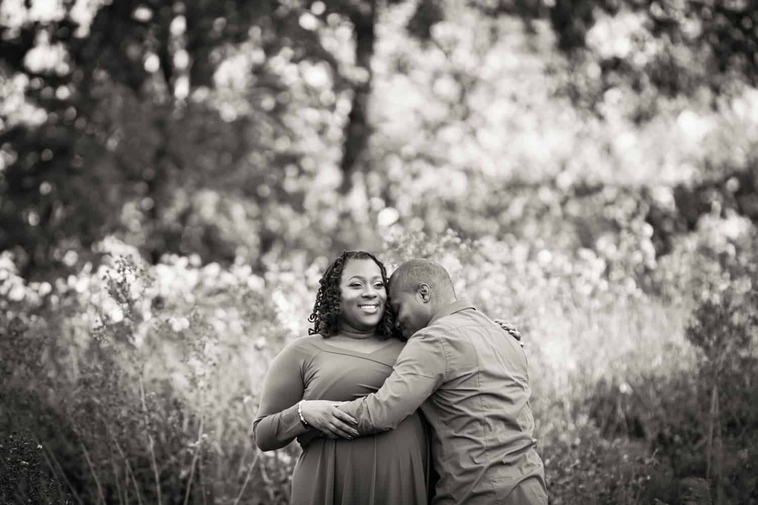 Black and white photo of African American couple cuddling in Forest Park