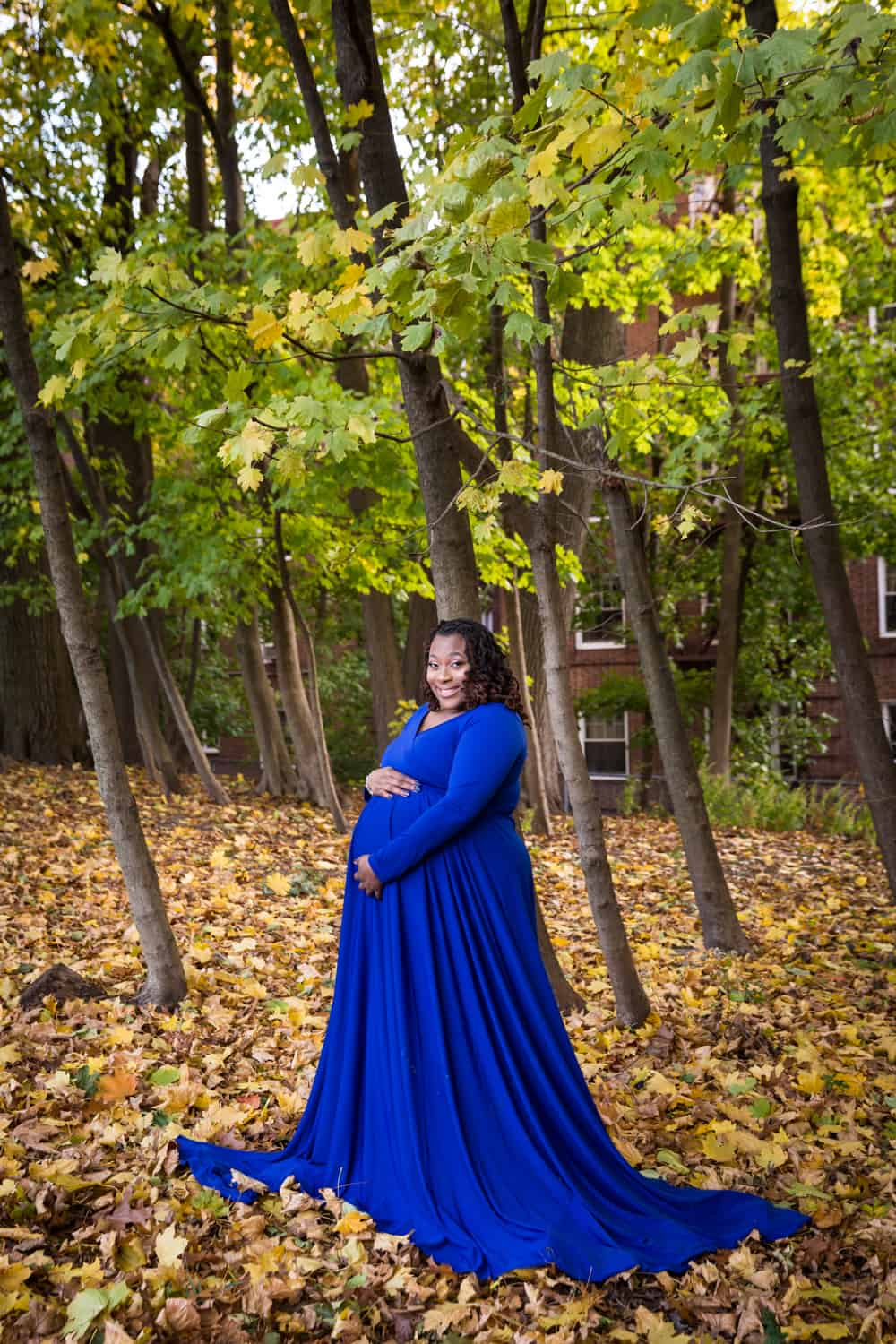 African American pregnant woman touching stomach and wearing blue dress in Forest Park