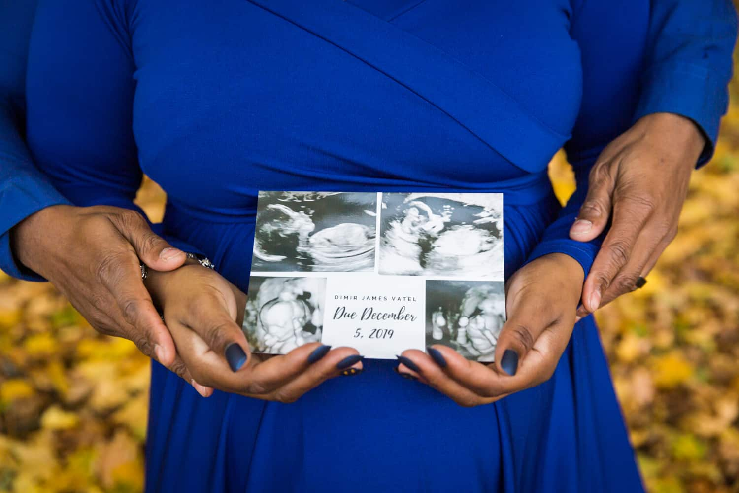 Close up of couple's hands on woman's pregnant stomach and holding birth announcement postcard