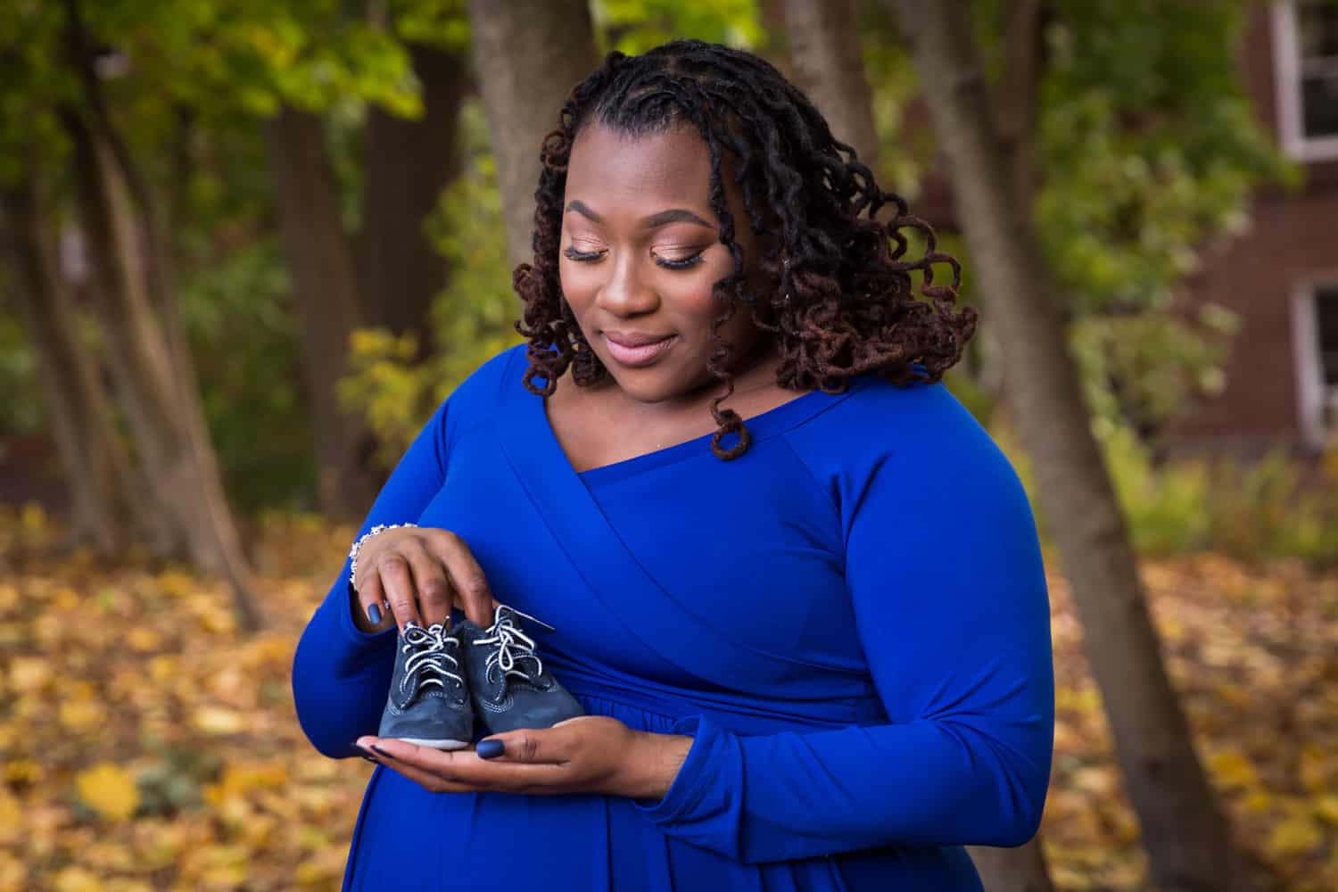 African American pregnant woman holding pair of baby shoes