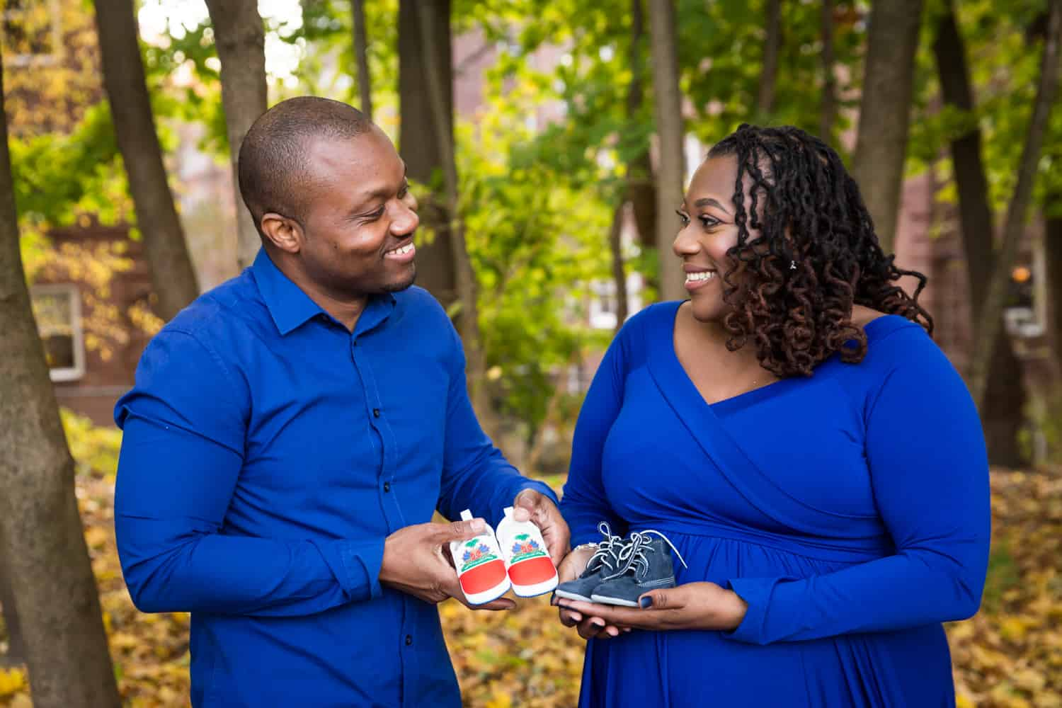 African American expecting couple each holding pair of baby shoes