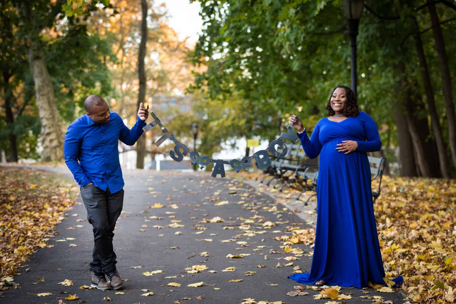 African American couple holding 'It's a Boy' sign in Forest Park pathway