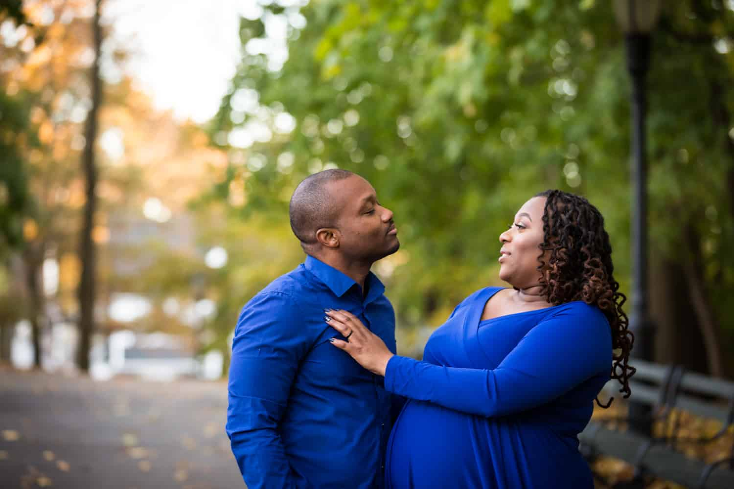 African American couple standing in Forest Park for an article on maternity photo shoot ideas