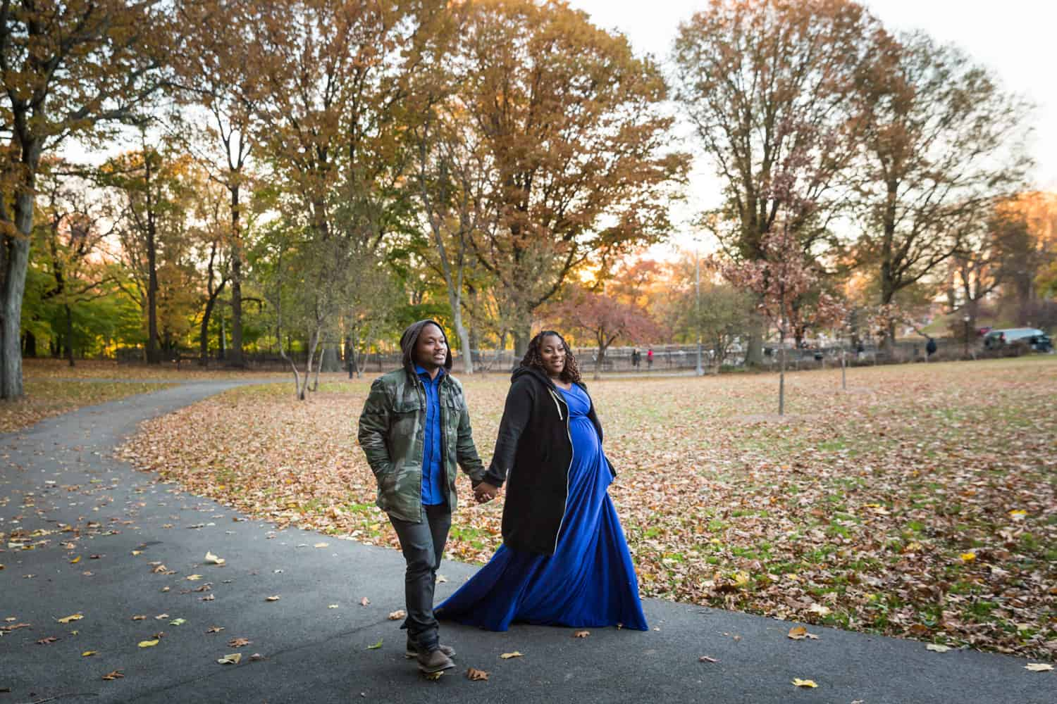 African American couple walking in Forest Park for an article on maternity photo shoot ideas