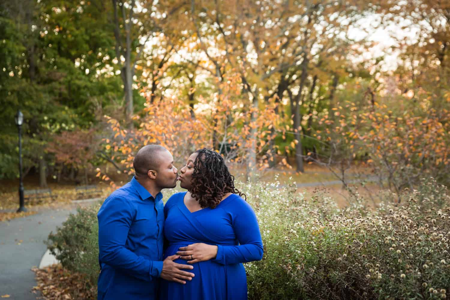 African American couple kissing in Forest Park for an article on maternity photo shoot ideas