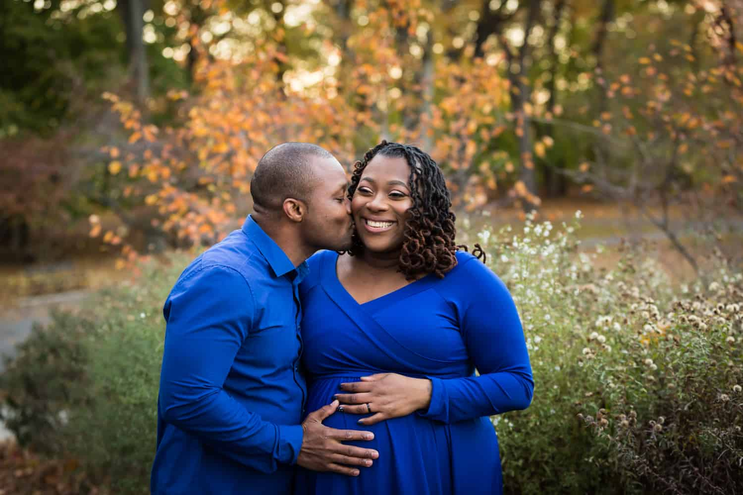 Man kissing woman's cheek during maternity photo shoot in Forest Park