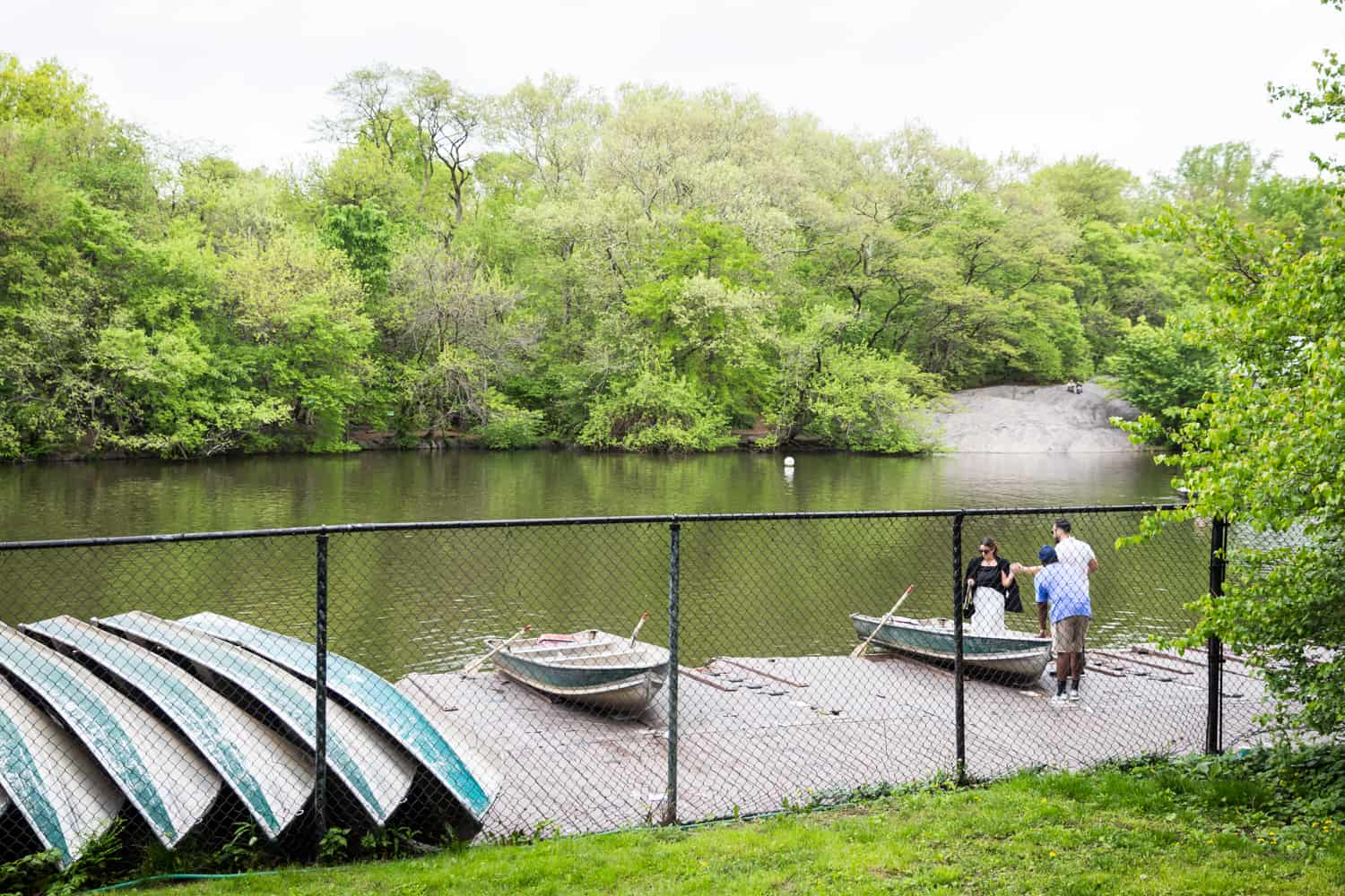 Man helping woman into boat at Central Park Boathouse