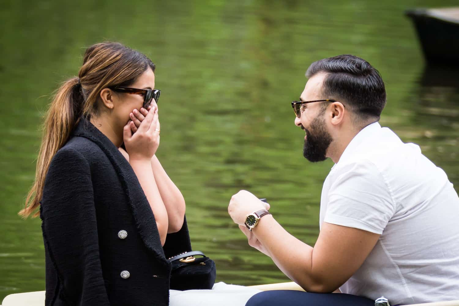 Woman gasping in surprise at a surprise proposal on Central Park Lake