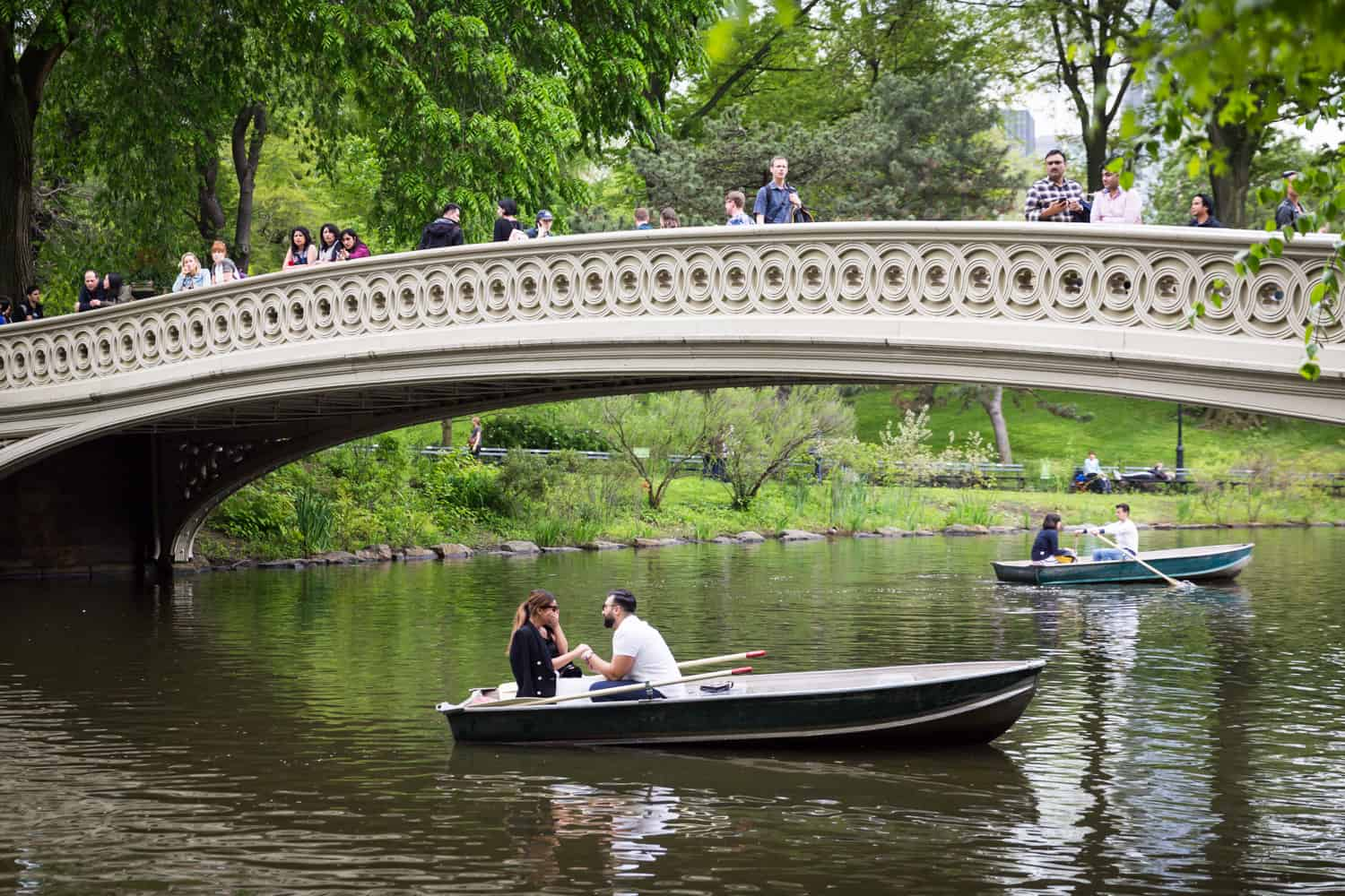 Man proposing to woman under Bow Bridge at a surprise proposal on Central Park Lake