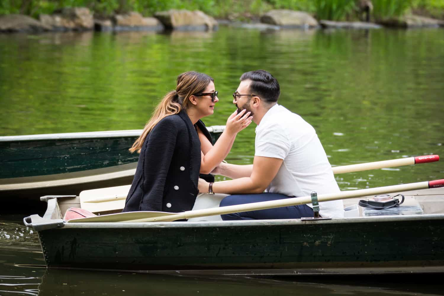 Woman touching man's face at a surprise proposal on Central Park Lake