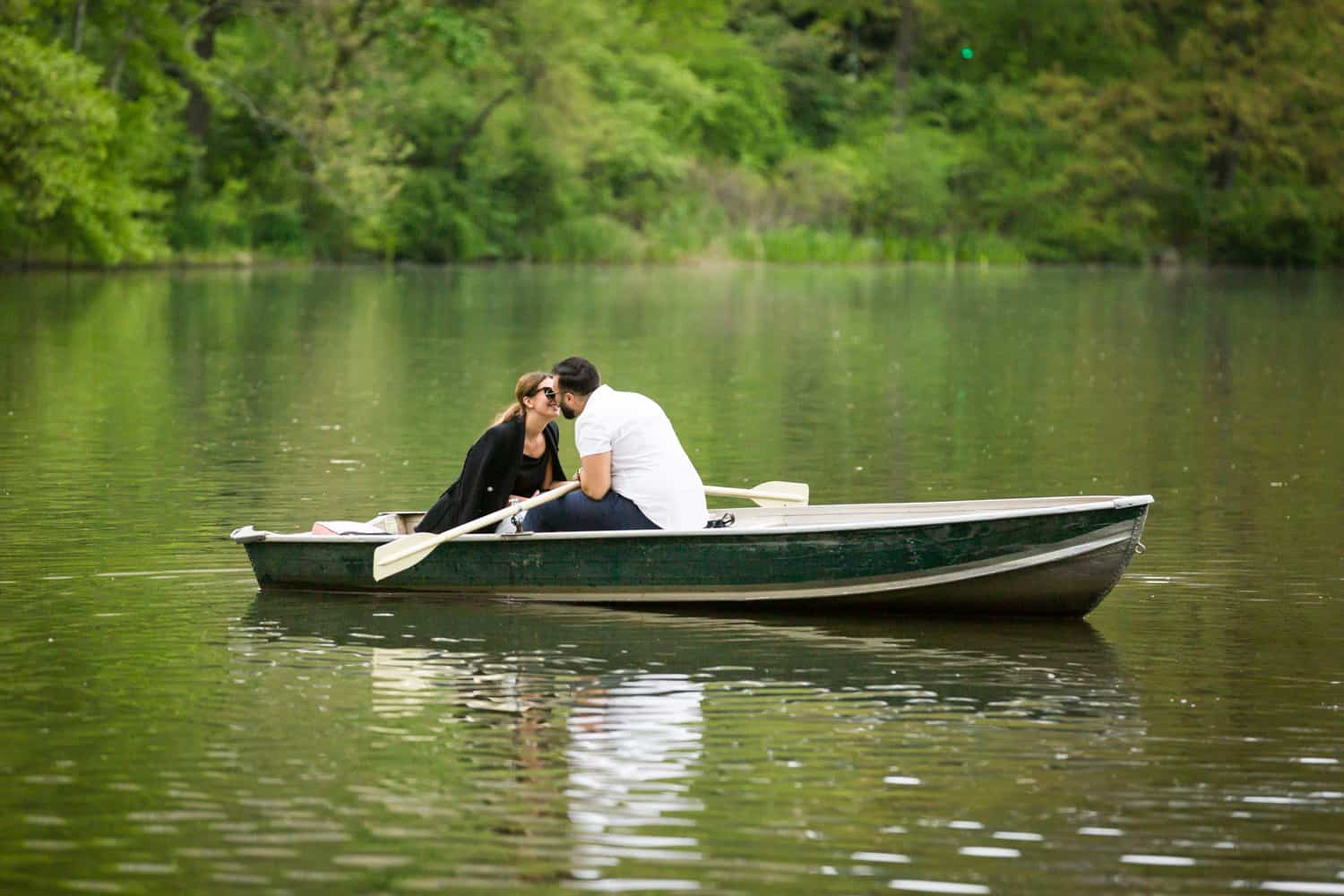 Couple kissing in boat at a surprise proposal on Central Park Lake