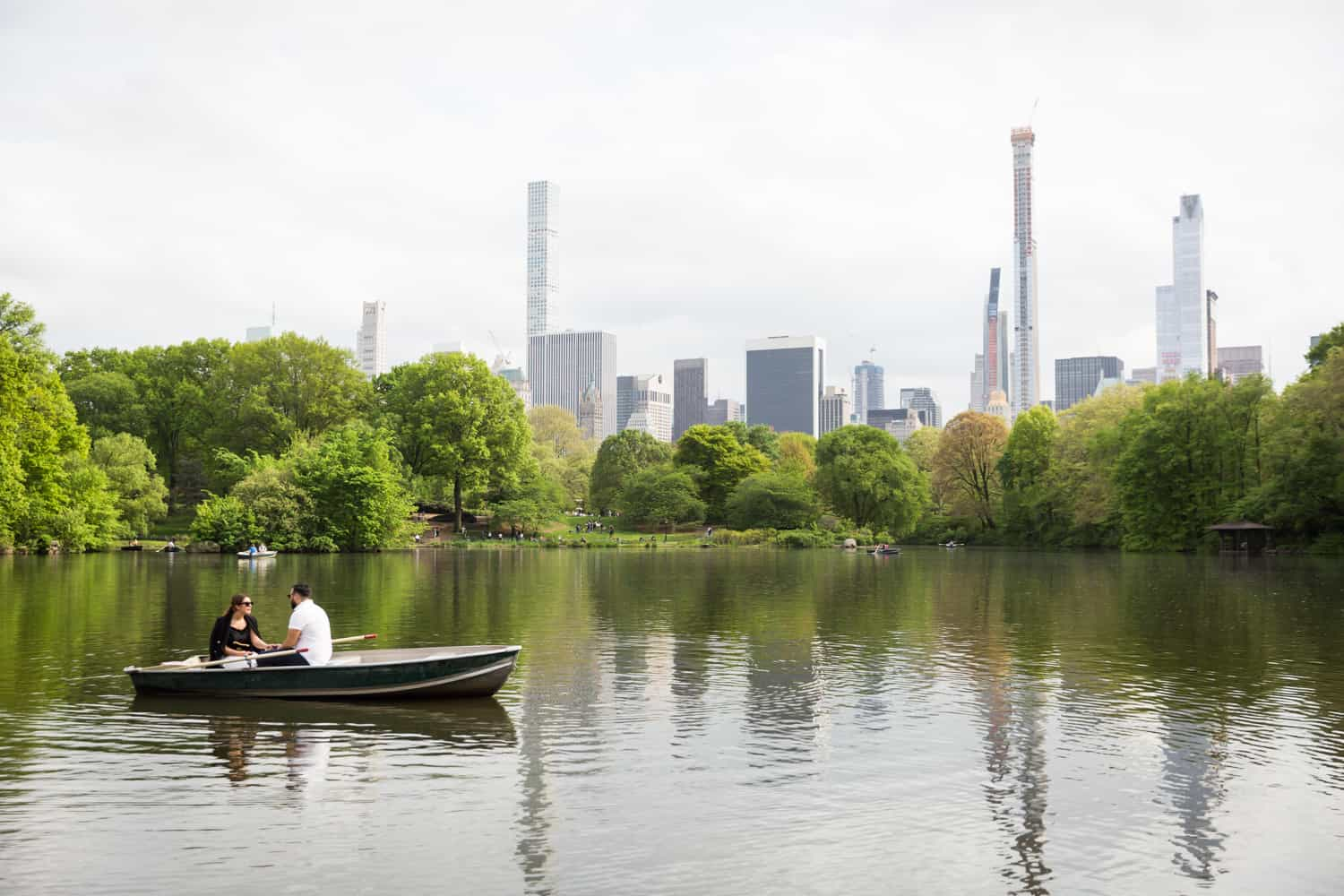 Couple in boat with NYC skyline in background at a surprise proposal on Central Park Lake