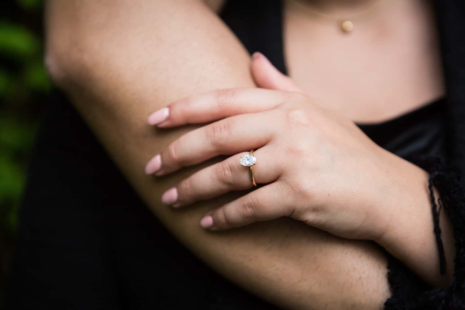 Close up of woman's hand with engagement ring resting on man's arm