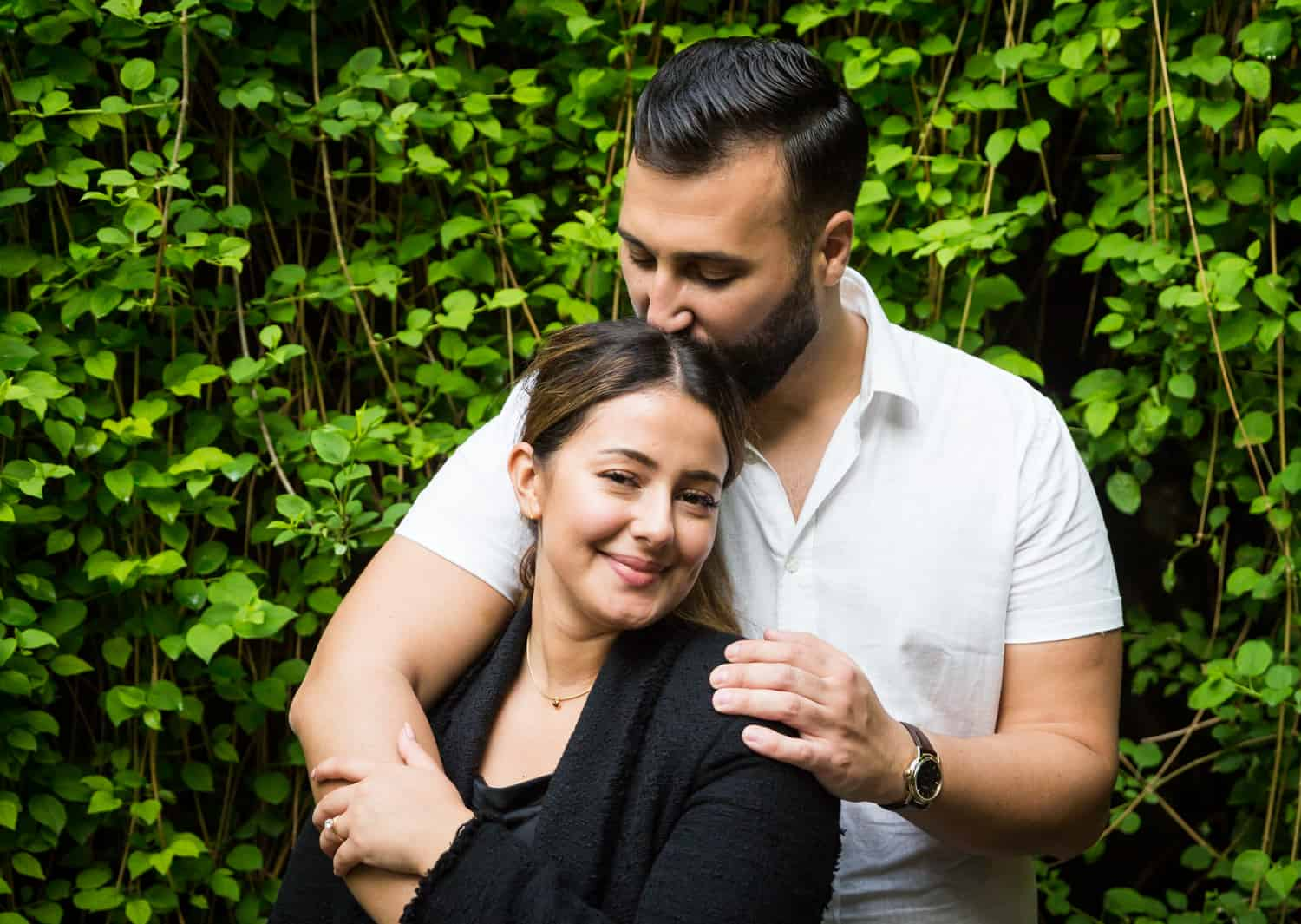 Man kissing woman's head in front of ivy-covered wall