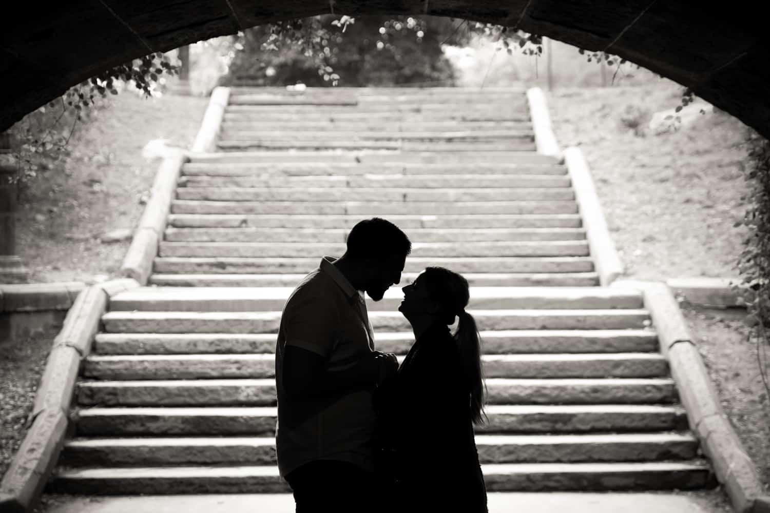 Black and white photo of backlit couple standing in front of staircase