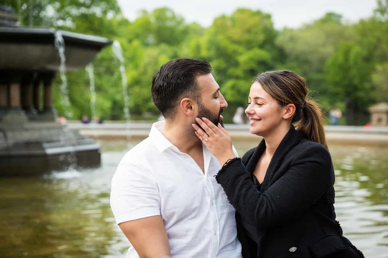 Woman touching man's cheek in front of Bethesda Fountain
