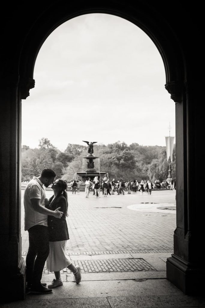 Black and white photo of couple standing in archway leading to Bethesda Fountain