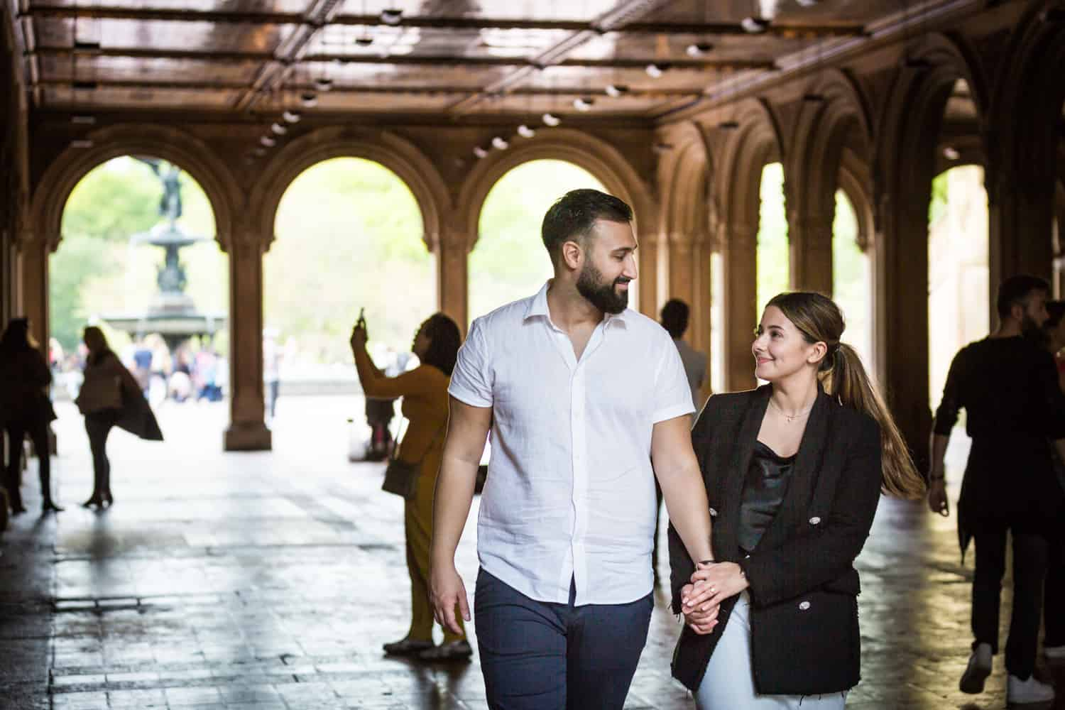 Couple walking hand-in-hand through Bethesda Terrace in Central Park