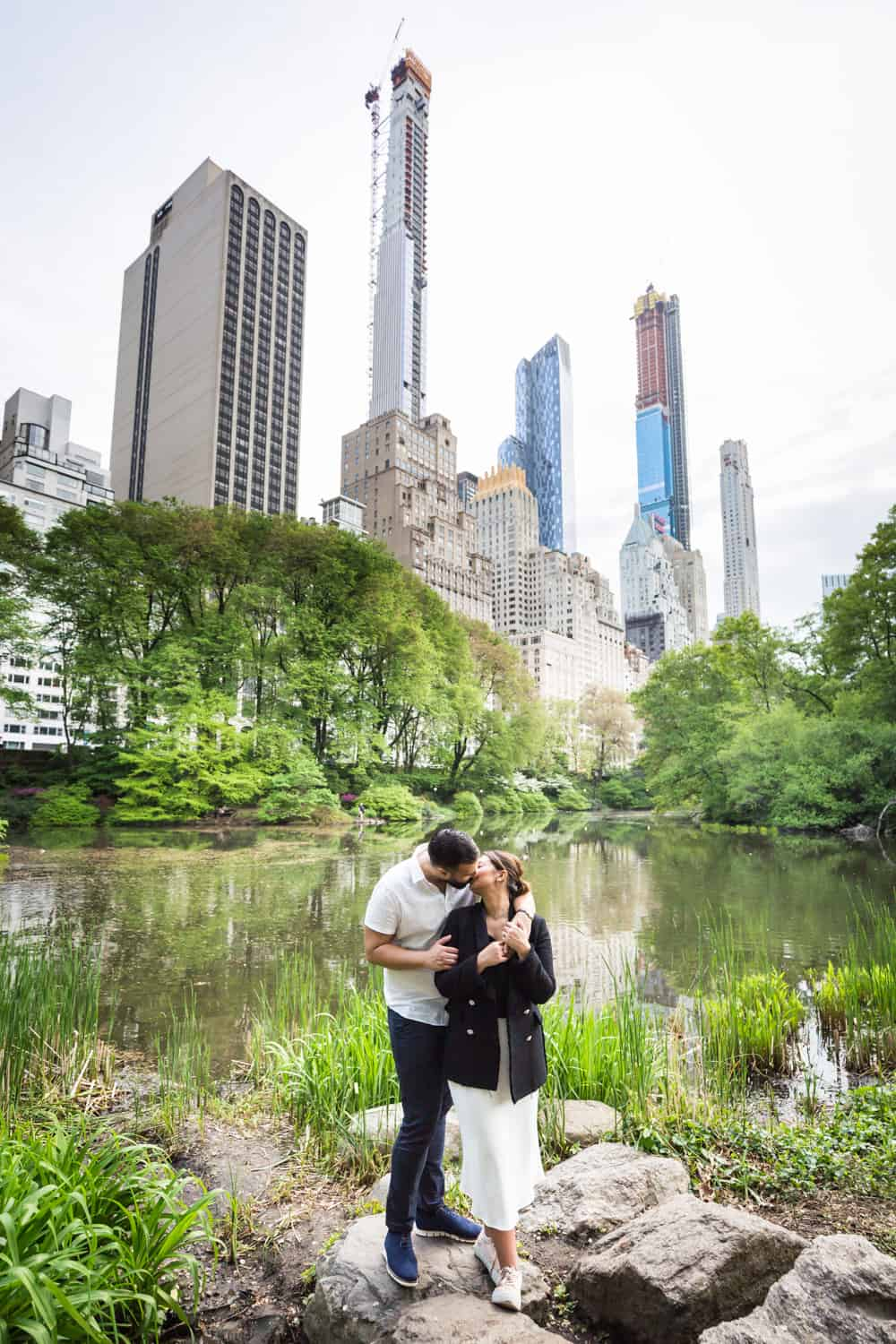 Couple kissing in front of Central Park pond