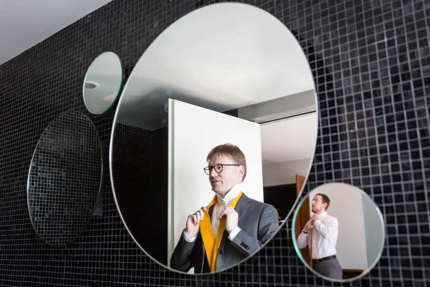 Groom getting ready in mirror with best man reflected in other mirror