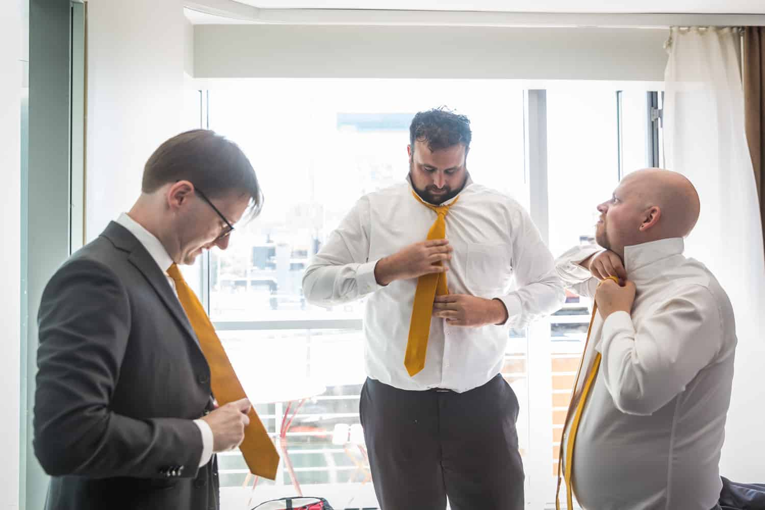 Groom and groomsmen fixing ties in front of window