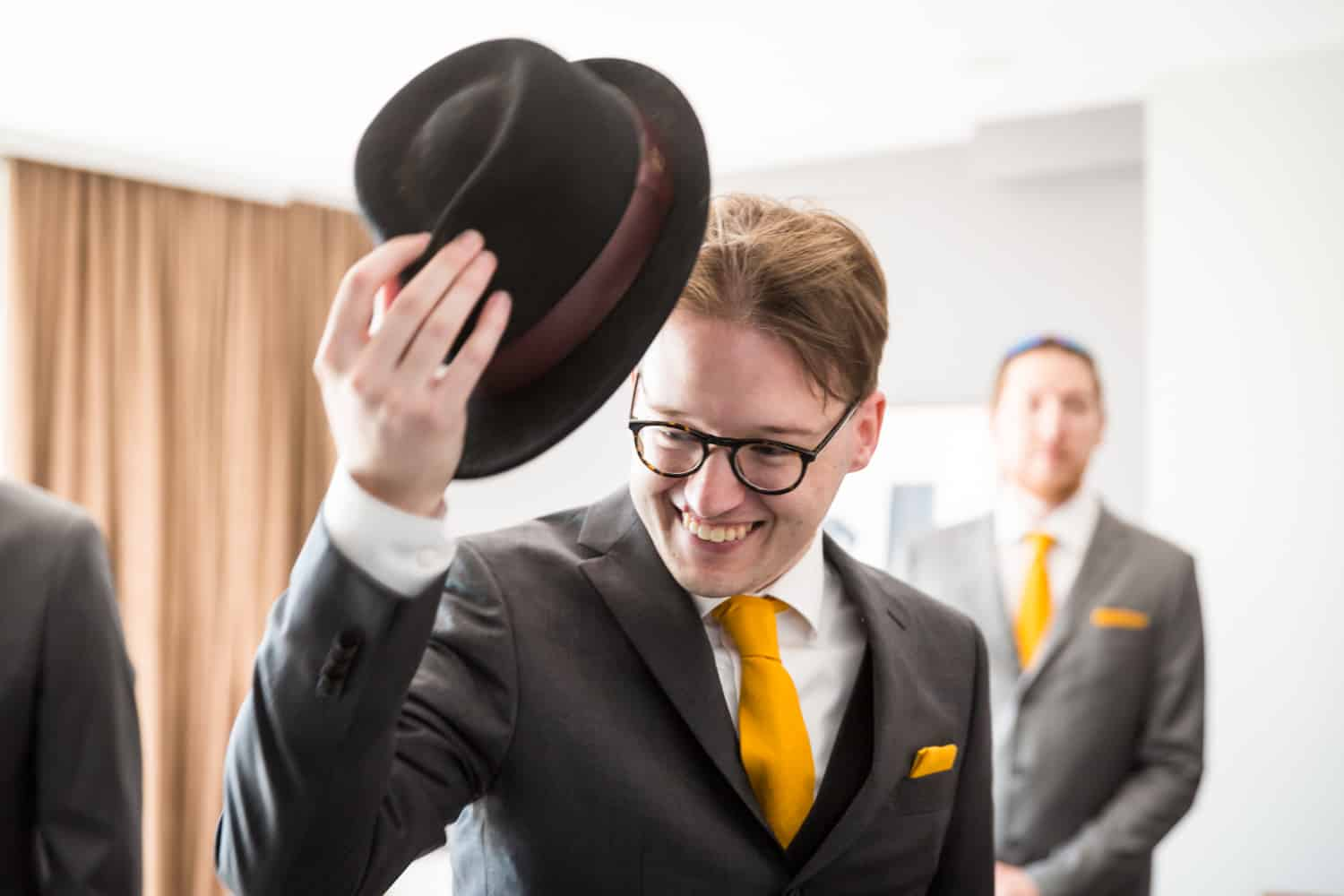 Groom pulling off hat in hotel room