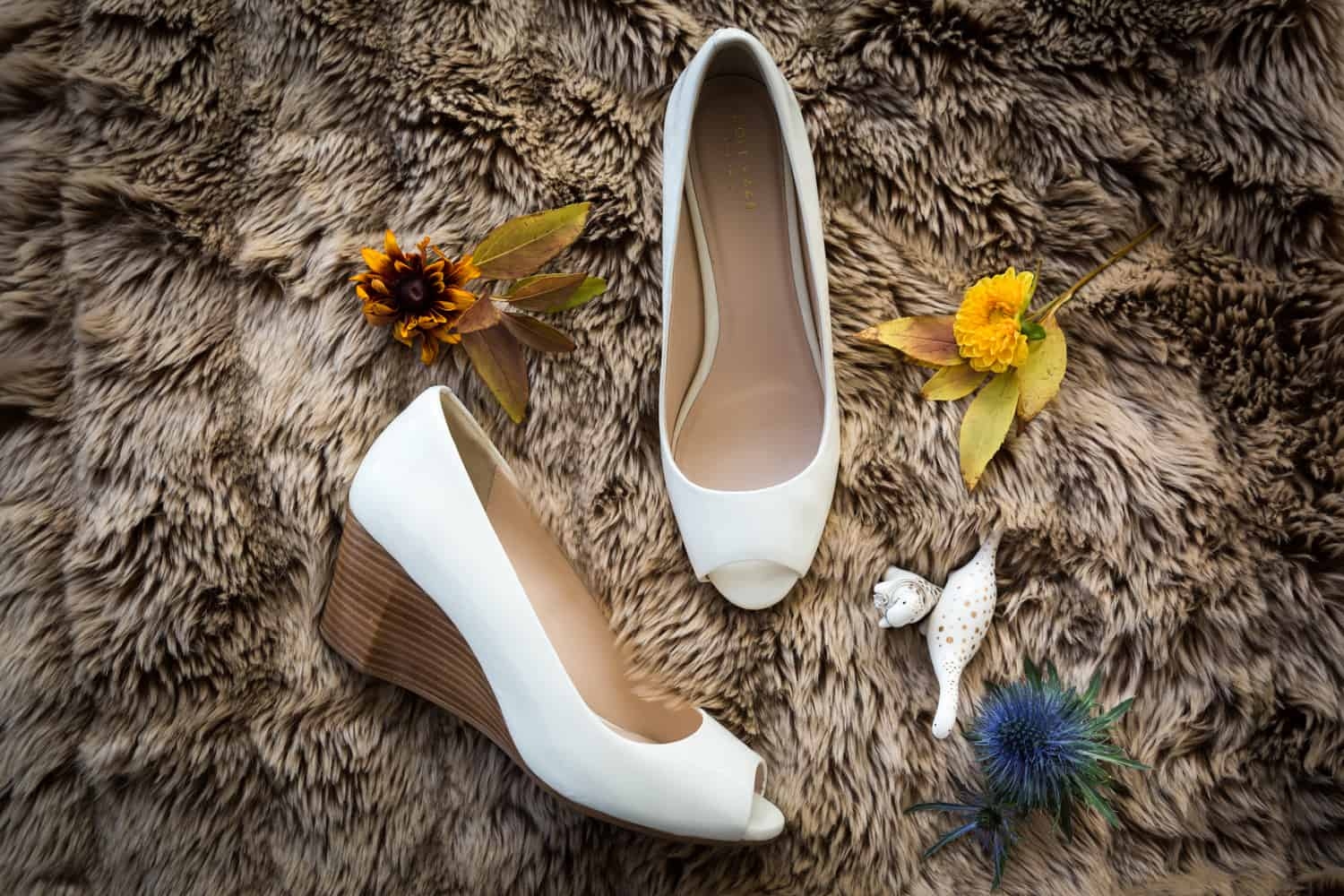 Bride's white wedge heels flowers and jewelry on furry rug