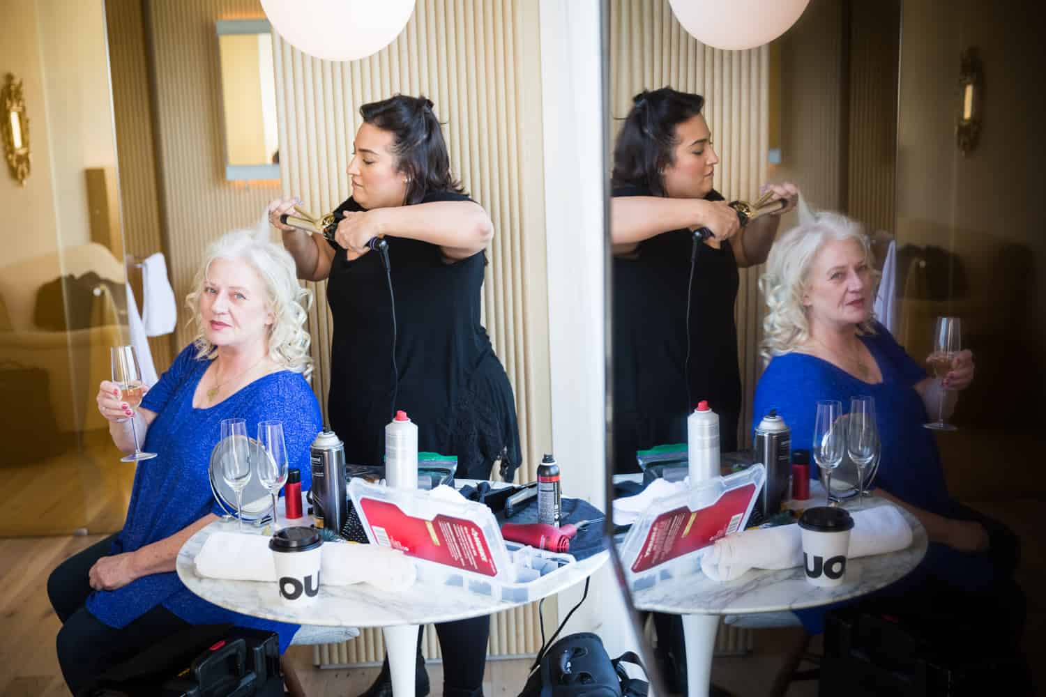 Mother of bride getting hair fixed with reflection in wall