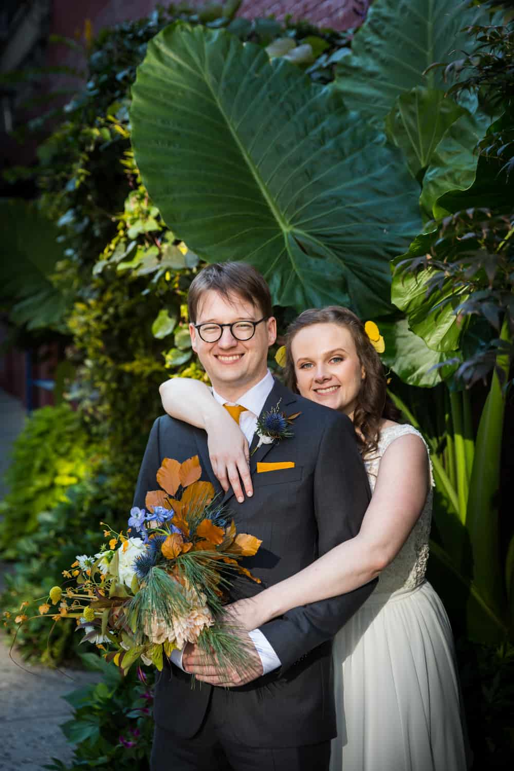 Bride and groom surrounded by plants for an article on Covid-19 wedding planning